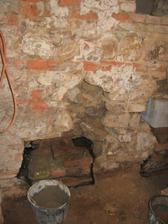 Vyloupat ze stěny kameny vymazat betonem do roviny pak izolaci, cihle a izolaci a vyzdít