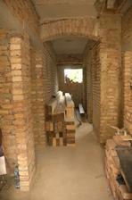 Dole v chodbě už všechny zdi obouchány a tam na zemi se rozvalují trámy na podlahu v podkroví