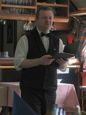 pan číšník čte menu, všichni poslouchají a těší se