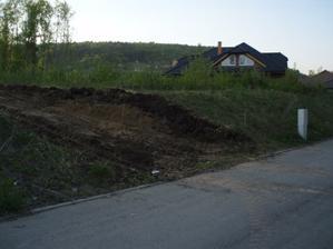bagr vytvořil i nájezd na pozemek. Musíme ho nějak zpevnit, po dešti se tam vše boří. Sklon se upraví podle výšky carportu dodatečně.
