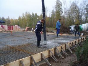 vzadu chlapi používají vibrátor na beton
