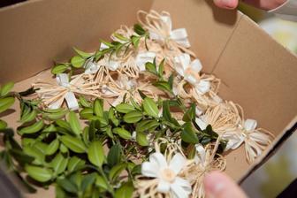 Vývazky (kytička z lýka, na tom kytička ze stuhy, sešito dřevěným knoflíkem, připnuté společně s buxusem)