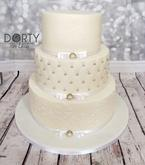Svatební dort s ostrými hranami (sharp edges), se spodním patrem zdobeným královskou glazurou, prostředním patrem zdobeným efektem prošívání a horním patrem s ručně vyvedenými iniciály