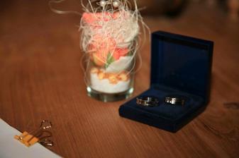 svatební prstýnky ještě v krabičce a pozadí polštářek z květu růže na prstýnky